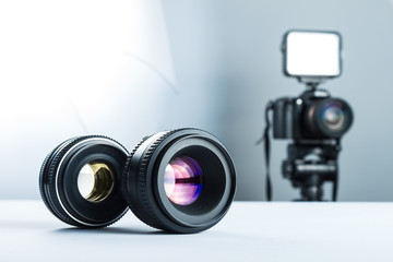 Two lenses on a white table in stuidio, against the background of the DSLR camera to light and softbox.
