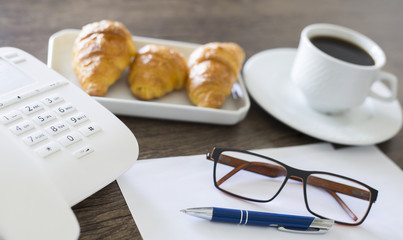 Office workplace. Croissants with coffee and telephone on the wooden table