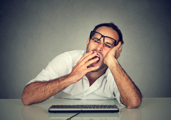 Sleepy worker man working on computer yawning