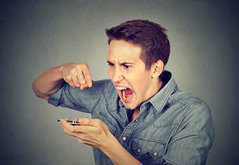 angry young man screaming on mobile phone i