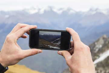 Black phone in man's hands making photo of mountains landscape