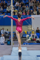 Gymnast doing a exercise on the Balance Beam. View from the back. Selective focus.