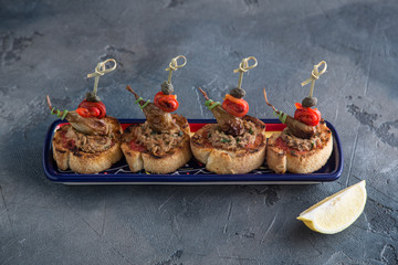 Spanish tapas. Montaditos. Bread slices with tuna, peppers and capers. Typical appetizer.