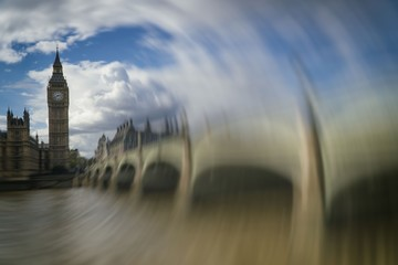 Big Ben with bridge against cloudy sky, London, United Kingdom