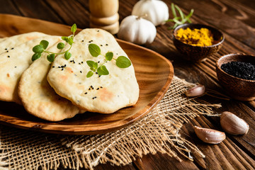 Traditional Indian Naan bread with garlic on a wooden background