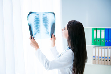 Female doctor looking at X-rays picture of patient's lung