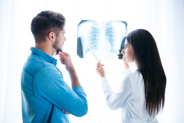 Young doctor showing the X-Ray photo of lung to her patient
