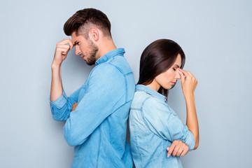 Two sad lovers standing back to back after quarrel