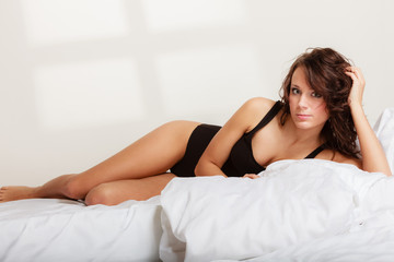 Sexy girl lazy woman in underwear lying on the bed