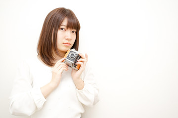 Young woman holding a camera with smile