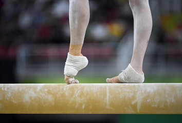 Foto op Plexiglas Gymnastiek Female gymnast on balance beam during competition