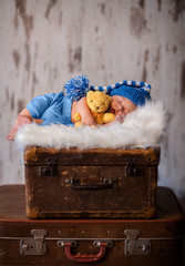 Newborn photography of 2 weeks old sleeping baby on soft fluffy