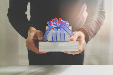 gift giving,man hand holding a gift box in a gesture of giving