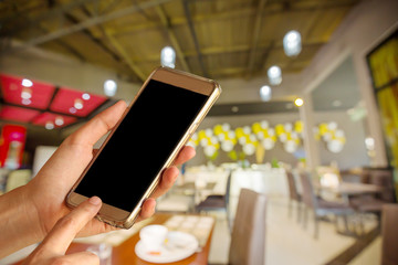 Woman hand hold and touch screen smart phone over blurred restaurant background