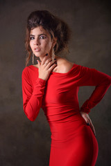young and slender girl model with dark hair and in a red evening dress