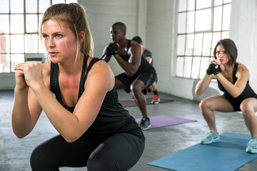 Team yoga class female trainer leading group in fitness squat calorie burning exercise