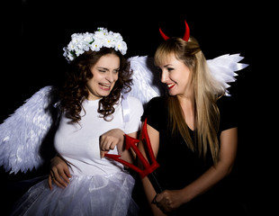 Portrait of angel and devil womans on a dark background