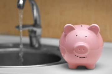 Pig money box beside kitchen sink and tap. Saving water concept