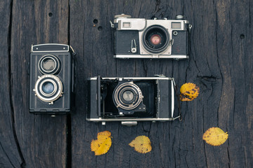 Old film camera on grunge dark wooden background
