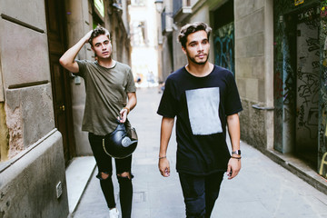 Two young men walking in the street.