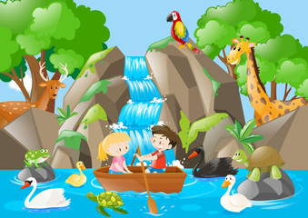 Kids rowing boat in the river full of animals