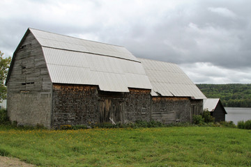 Old weathered barn with tin roof in rural farmland