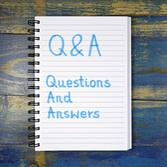 Q&A- Questions And Answers acronym written in notebook on wooden background