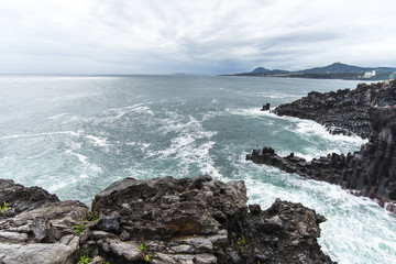 Pacific ocean and black volcanic lava in Jeju Island - South Korea