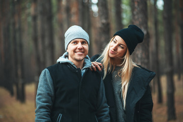 Portrait of young couple in love walking in beautiful forest enjoying hugging and smiling. Family in forest spending weekend.