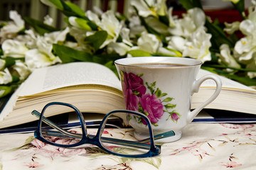 Concept image with open book, coffee cup, reading glasses with flowers in background.
