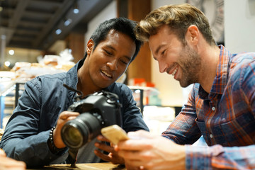 Guy friends in coffee shop checking pictures on photo camera