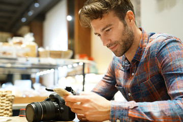 Man in coffee shop checking pictures with camera and smartphone
