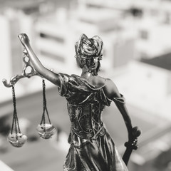 Back view of Lady Justice, statuette of the Themis goddess. Law concept. City buildings outdoor background