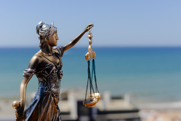 Sculpture of justice or themis goddess on outdoors bright blue sky background