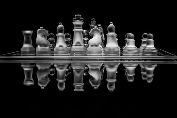 Black and white glass chess set with reflection