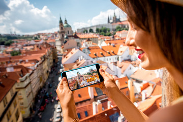Young female tourist photographing with phone a beautiful cityscape of the old town of Prague