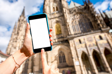 Holding phone with white screen on the famous cathedral background in Prague city