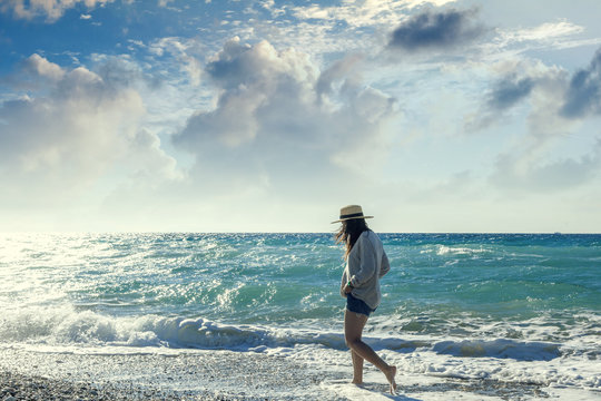 Young woman in a hat walking along the seashore. Holidays and tr