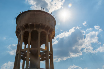 Looking up to a large cement reservoir with clouds behind the water tower