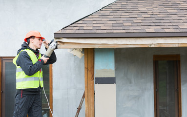 worker dismantling roof shingles