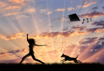 Girl with dog running with a kite