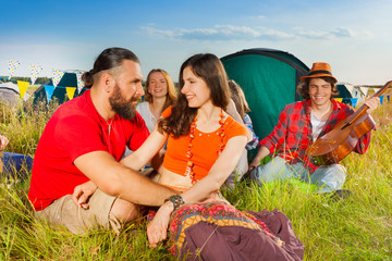 Young couple in love sitting on grass at campsite