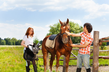 Happy equestrians preparing their horse for riding