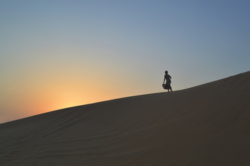 girl in the setting sun in the desert