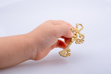 Child hand holding a retro styled key