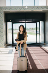young attractive girl with a suitcase goes on the terminal