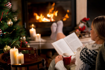 Woman is sitting with cup of hot drink and book near the fireplace