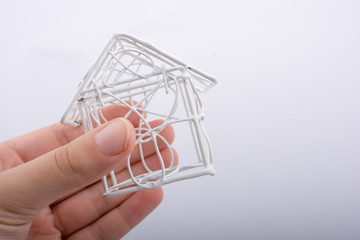 Little wired metal model house in hand