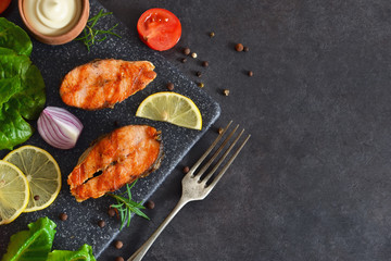 Salmon steak grilled with peppers and lemon on a black background