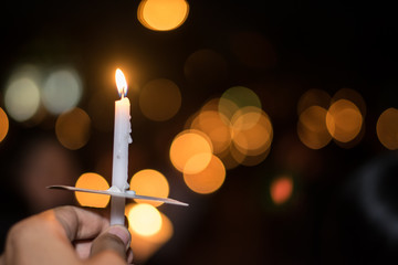 Blurred image for background of hand with candle memorable for King Bhumibol Adulyadej of thailand
